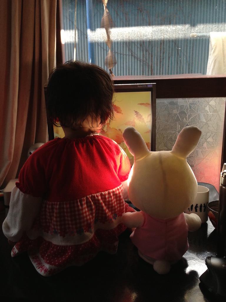 うさぎのぬいぐるみと並んで座って映像を観る子供