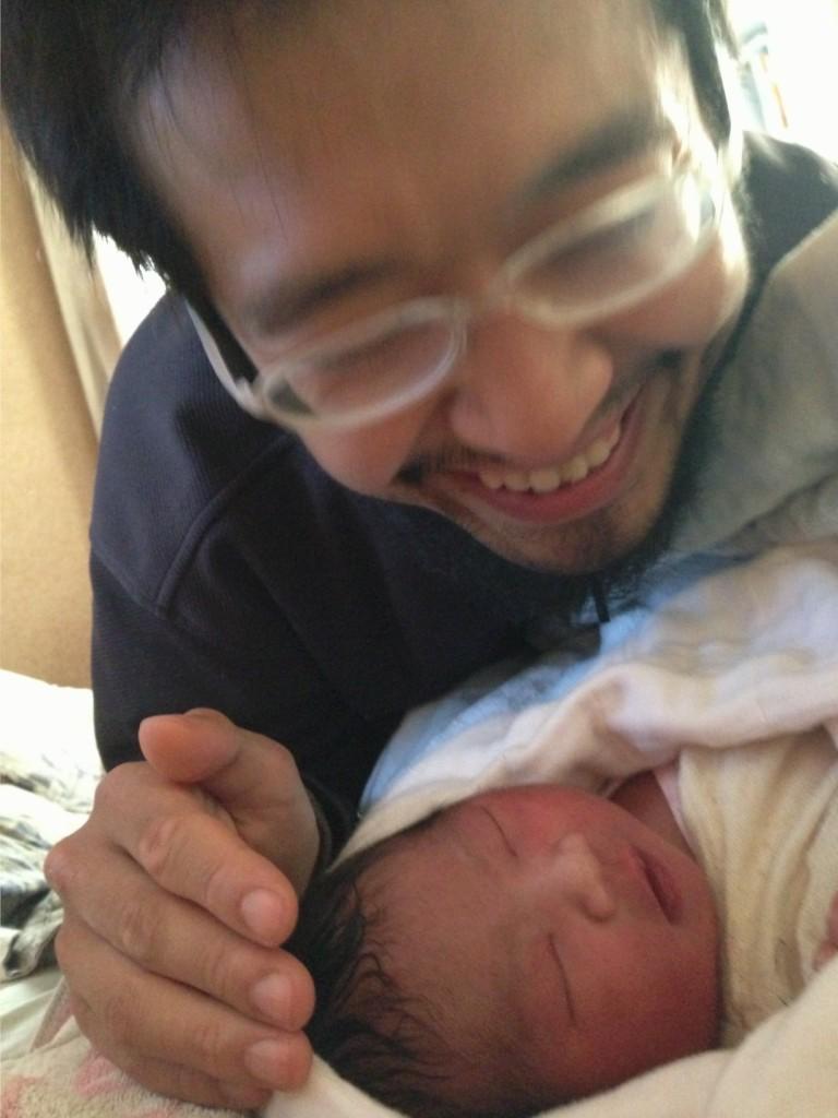 生まれたての自分の子供を見つめる父親