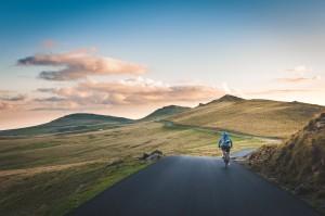 山と空が観える道を走る自転車