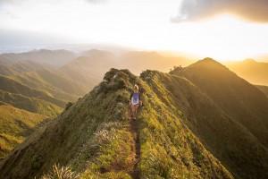 山の尾根を歩く女性