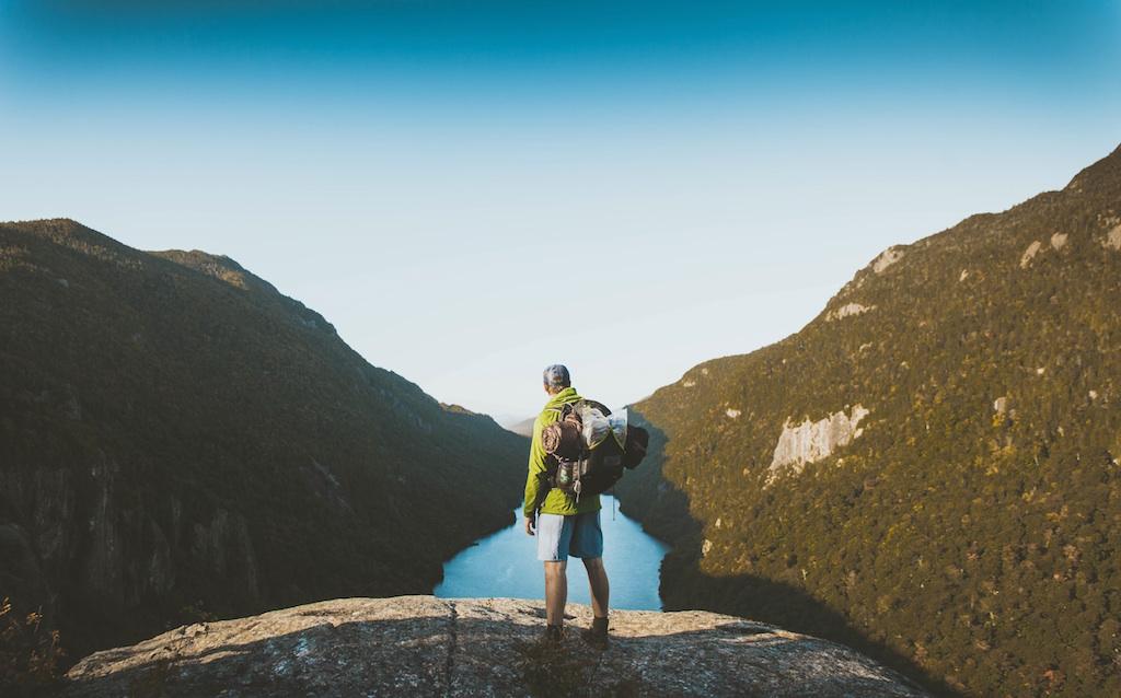 岩の上から山と湖を眺める男性